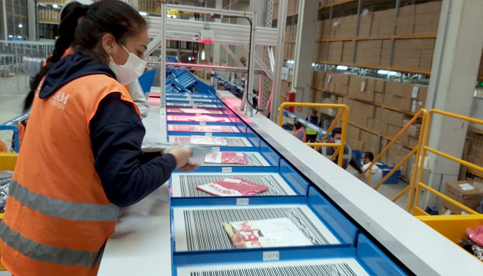 Manual infeed of fashion items into the sorter - BR Magazacilik